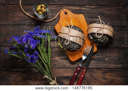 Delicious black burgers in craft paper and blue flowers on dark wood table.