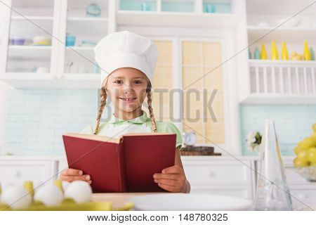 Pretty female child wants to cook something delicious. She is holding cookbook and looking at camera with aspiration. Kid is standing in kitchen and smiling