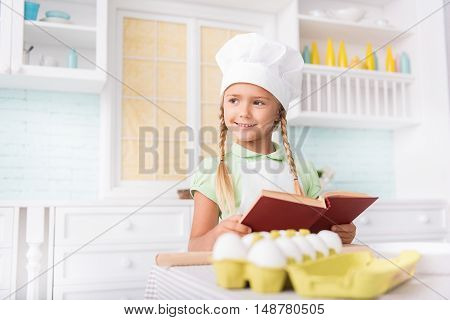 Cheerful girl is dreaming of being chef. She is standing in kitchen and looking aside pensively. Child is holding recipe book and smiling