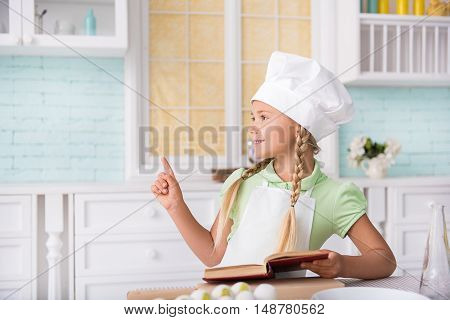I have a great idea. Pensive girl is preparing for cooking. She is holding cookbook and pointing finger up. Child is standing near table in kitchen and laughing