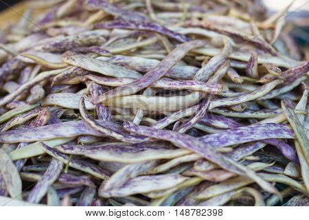 Pile of yellow red string beans at farm market. Runner beans. String beans background