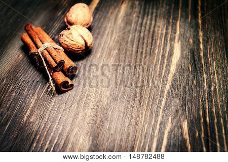 Cinnamon sticks tied together with ribbon on wooden table close up with copyspace