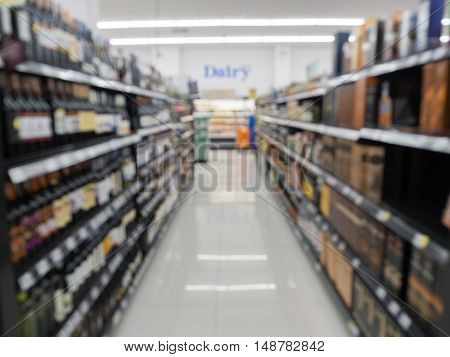 Blurred alcoholic drinks on shelf in the supermarket