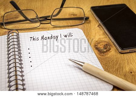 Plans for Monday concept - Conceptual image with organizing the plans for the beginning of the week on a math spiral notebook. Eyeglasses a pen and a phone are in the background.
