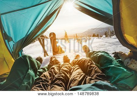 Group of friends snowboarders and skiers relaxing in tent on background of sunset and mountains valley. Sheregesh resort, Siberia, Russia