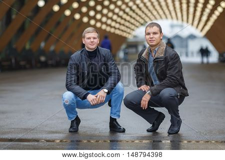 Portrait of two young men sitting on his haunches on background of lights installation main park alley