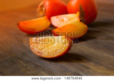 Fresh Persimmon fruit. ripe persimmon on a wooden background . Persimmon cut into pieces. close-up