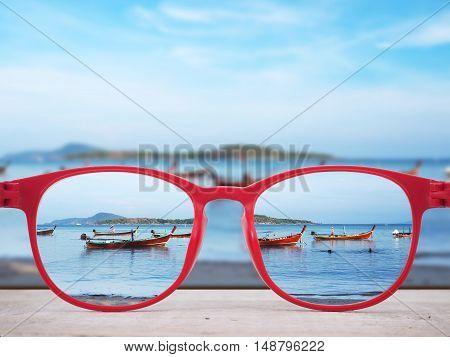 Summer beach at Phuket Thailand focused in red glasses lenses