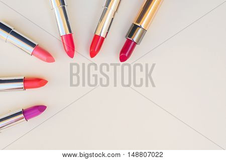 Collection of puple, pink and red shiny lipsticks, top view with copy space