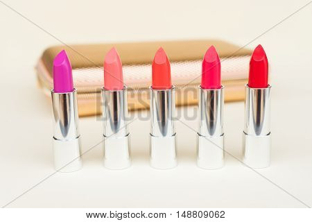 Collection of puple, pink and red shiny lipsticks in front of golden woman pursue