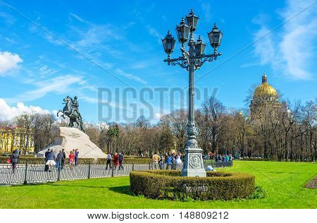 SAINT PETERSBURG RUSSIA - APRIL 25 2015: The beautiful old fashioned streetlight in Senate Square with the Bronze Horseman and the dome of St Isaac's Cathedral on the background on April 25 in Saint Petersburg.