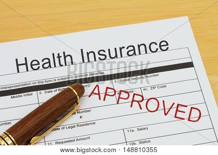 Applying for a Health Insurance Approved Health Insurance application form with a pen on a desk with an approved stamp