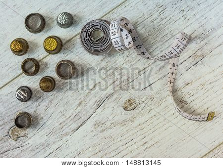 tapeline and old thimbles lie on the light board