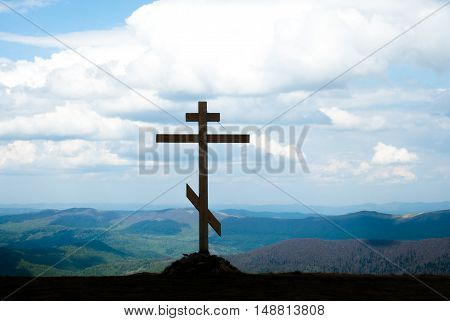 The cross on top of the mountain. Cross against the sky. Wooden cross on a hill. Christian cross. The cross on the background of mountains.