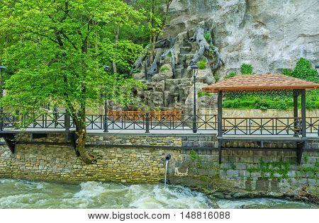 The embankment of Borjomula river with the small alcove for tourists Borjomi Georgia.