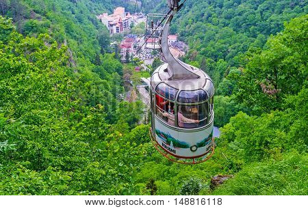 BORJOMI GEORGIA - MAY 27 2016: The aerial tram rides down from the upper Plateau Station to the mineral water park located in green gorge on May 27 in Borjomi.