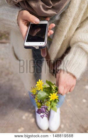 woman holding a beautiful bunch of wild spring flowers and taking photo of it with her smartphone. Bouquet of yellow and blue flowers in hands. Making picture by the telephone.