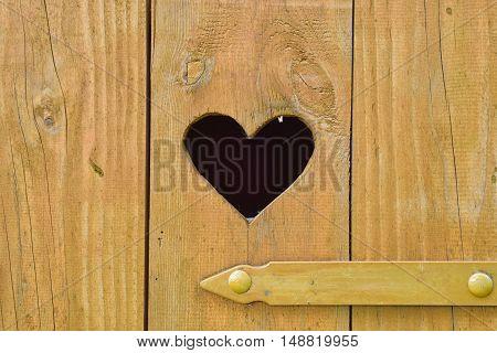Detail of a heart on door of wooden toilet.