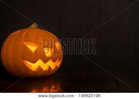 Halloween pumpkin with fire candle glowing on dark backdrop with reflection. Creepy face on halloween pumpkin from right side. Soft focus.