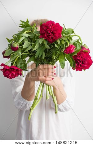 Woman holding beautiful red peonies. Girl with bouquet of flowers in her hands. Closeup of hands holding peonies.