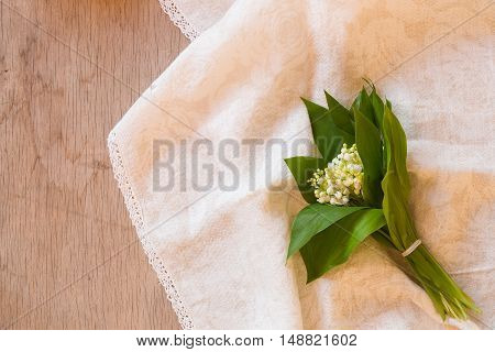 Bouquet of lilies of the valley. Bunch of lilies of the valley on the white cloth and rustic wooden floor. Horizontal background