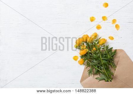 Top view on beautiful yellow garden flowers in the craft envelope on the white wooden background. Bouquet of flowers. Card. Greetings. Holidays and spring concept