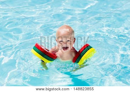 Happy laughing baby boy playing in outdoor swimming pool on a hot summer day. Kids learn to swim. Child with colorful armbands. Family vacation in tropical resort.