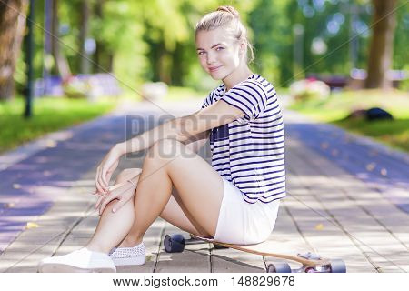 Teenagers Lifestyle Concepts and Ideas. Positive Blond Caucasian Girl Posing With Longboard in Park Outdoors. Horizontal Shot