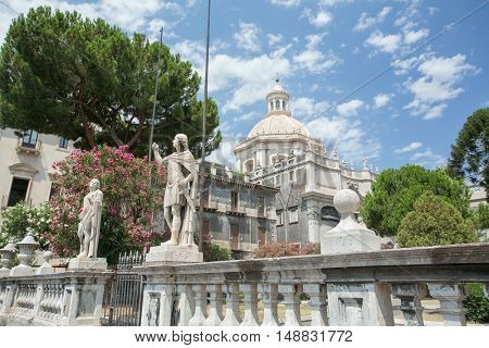 The Statue of St Agatha, the patron of Catania, surrounded by blooming trees of the Cathedral's garden, with the great dome of the St Agatha Abbey Church on the background, Sicily, Italy.