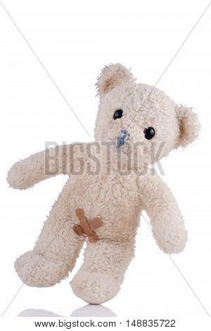 Toy bear with adhesive bandages on his private parts front view