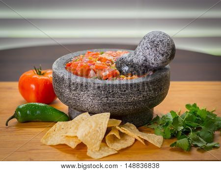 A freshly made mortar of salsa fresca, with Tomato green peppers and chips, in a molcajete and  cilantro