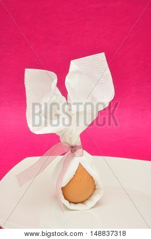 An egg tied in a serviette that looks like bunny ears for easter displayed on a plate