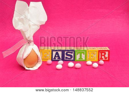 An egg tied in a serviette that looks like bunny ears for easter displayed with candy and alphabet blocks spelling easter on a pink background