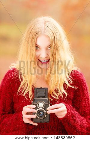 Portrait of pretty smiling woman in fall forest park with old vintage camera. Happy gorgeous young girl passionate photographer. Autumn winter photography.