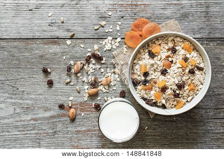 homemade muesli with dried fruits and milk on rustic wooden background. top view. healthy breakfast