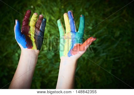 a child painting with fingers and palms paints. funny and creative. Green grass background
