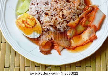 barbecued red pork dressing sweet sauce with brown rice on dish