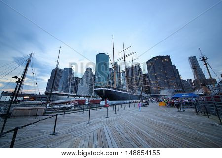 NEW YORK, USA - SEP 07, 2014: Historic ships in front of the skyscrapers in the South Street Seaport in the evening