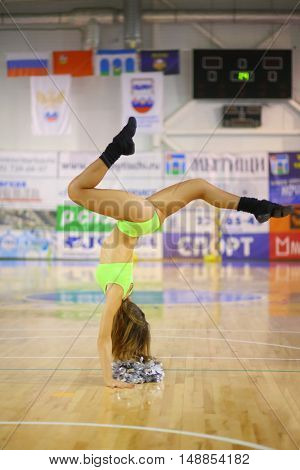 MYTISHCHI, RUSSIA - OCT 16, 2014: Girl cheerleader (with model release) in a light green suit performs a handstand in the gym on the Russian Futsal Super League in Mytishchi