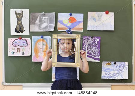 MOSCOW - MAR 20, 2015: Girl (with model release) looking through decorative frame. School 430 operating since 1981.