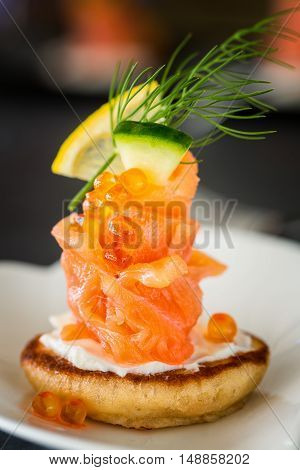 One Blini appetizer with smoked salmon and sour cream garnished with dill. Close-up view