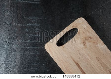 Wooden cutting board on black stone background. Top view