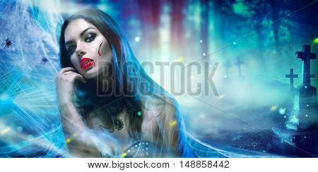 Beautiful Halloween Vampire Woman portrait. Beauty Sexy Vampire Vitch lady with blood on mouth posing in cementery, wearing spider web. Fashion Art design. Misterious Model girl with Halloween make up