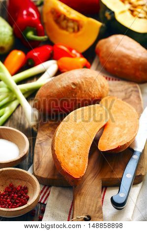 Sweet potatoes and autumn vegetables on wooden cooking board