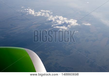 view from a plane window at the clouds and the earth