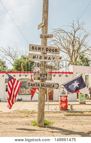 ADRIAN TEXAS - AUGUST 25 2013: Halfway point on Route 66 where it is 1139 miles to Los Angeles to the west and Chicago to the east. Note the Phillips 66 gas pump and the rusty Coca Cola machine.
