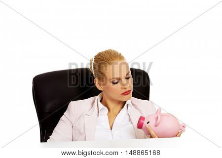Angry business woman looking for her piggybank and sitting behind the desk