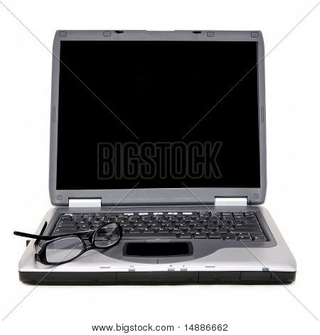 Laptop with glasses on keyboard