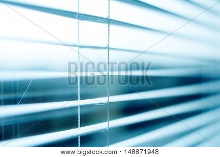 blinds, jalousie, arching, white blinds, window can be seen through open jalousie, light passes through the raised blinds Office. The weather outside. Winter. Cold. conceptual photo blinds.