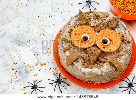 Owl cake - Halloween or birthday party dessert delicious cream cake in the form of an funny owl. Halloween cake on a festive decorated table creative idea for treats